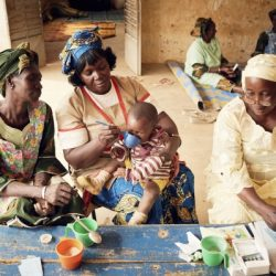 Three women help administer malaria medication to a child